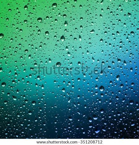 Raindrops on a window pane. Droplets of water on the glass. Water drops background. - stock photo