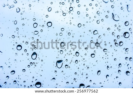 Raindrops on a window pane on the background of a stormy sky. - stock photo