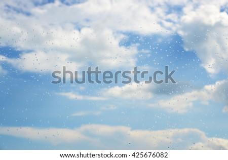 Raindrops on a window.Through the glass sky and clouds - stock photo