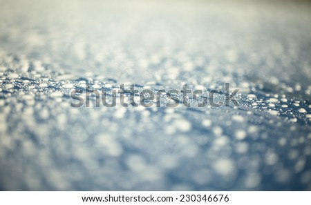 Raindrops on blue sky metal surface - stock photo