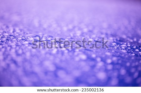 Raindrops on purple surface metal - stock photo