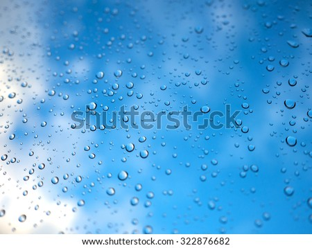 Raindrops on the glass with blurry blue sky and white cloud.