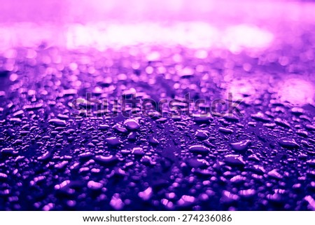 Raindrops on the metal surface in the light colored lights. Image in the purple-blue toning - stock photo