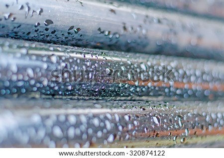 Raindrops on the pipes. Autumn rain. Pipes are one to one painted in black paint