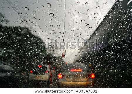 Raindrops on the windshield glass with blurry traffic background