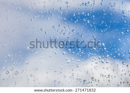 Raindrops on window glass against blue sky with white clouds - stock photo