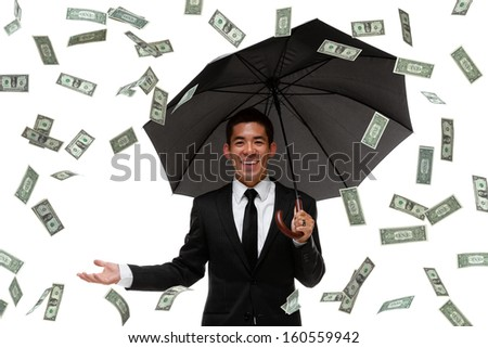 Raining money on a businessman with an umbrella - stock photo