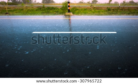 Raining on a road as the rain soaked streets. Rainy weather on a highway street. - stock photo