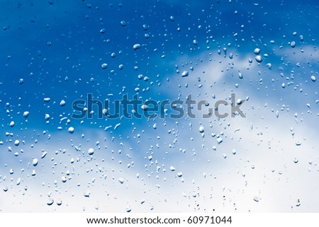 Rainsdrops on a window with a blue sky background