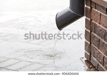 rainwater flow from the drainpipe installed on brick wall - stock photo