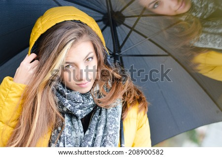 rainy day: closeup on young beautiful brunette woman having fun with umbrella wearing warm yellow coat or puffer on copy space outdoors background, portrait  - stock photo