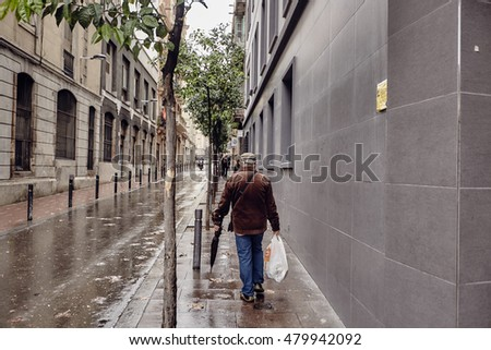 rainy day in Barcelona, people walking with umbrellas