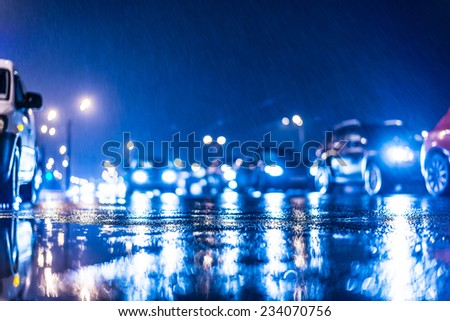 Rainy day in the city at night, stream of cars on the road - stock photo