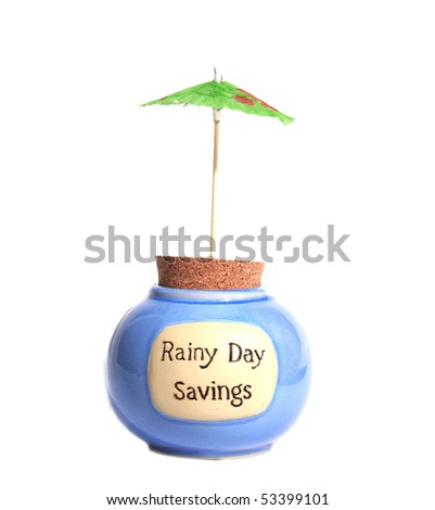 Rainy Day savings jar under umbrella - stock photo