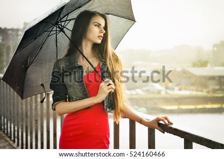 Rainy day. Young woman in red dress with umbrella standing on the bridge.