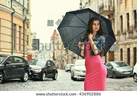 Rainy day. Young woman in red dress with umbrella standing on the street