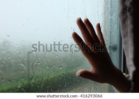 Rainy mood. Some person touching the window while raining day.