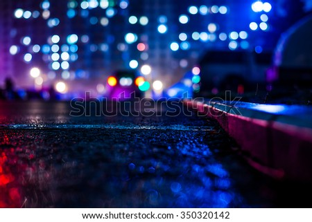 Rainy night in the big city, alley with cars on the background of glowing windows of the house opposite. View from the level of the curb on the road, in blue tones