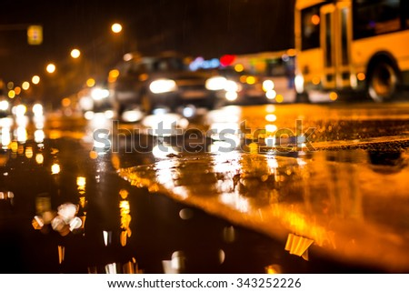 Rainy night in the big city, dense traffic at a busy intersection. View from puddles on the pavement level - stock photo