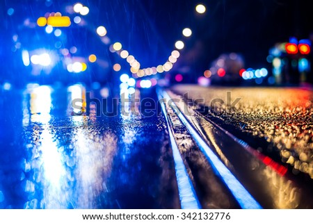 Rainy night in the big city, stream of cars traveling along the avenue. View from the tram rail level, in blue tones - stock photo