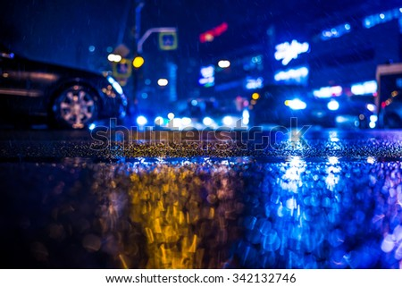 Rainy night in the big city, the car is at a crossroads. View from the level of asphalt, in blue tones - stock photo