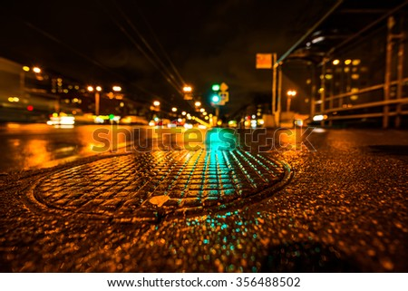 Rainy night in the big city, the glowing lights of approaching cars. Wide angle view of the level of a manhole on the pavement