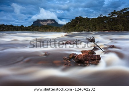 Rainy Season in the Venezuelan Jungle. Strong current of the river in the foreground with Tepui (mountain) in the background. Wild and clean green environment. - stock photo