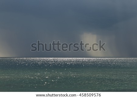 Rainy weather over the sea. Rain and the glare of the sun on the water surface and horizon all this created a scene for the amazing background. - stock photo