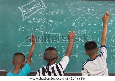 Raised hands in classroom at country School between classmate - stock photo
