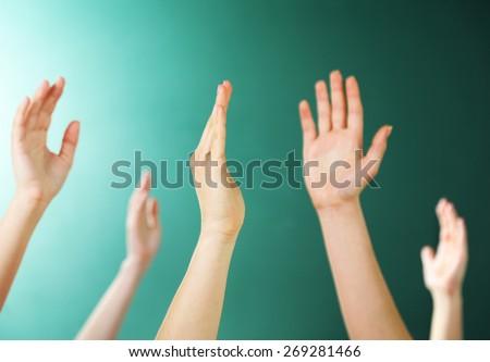 Raised hands on blackboard background in class - stock photo