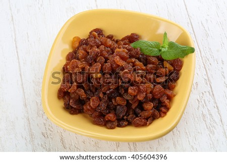 Raisin in the bowl on the wood background - stock photo