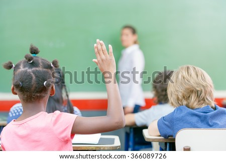 Raising hand at class lesson, primary school scene. Success and education concept. - stock photo