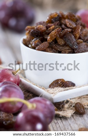 Raisins and Grapes on wooden background - stock photo