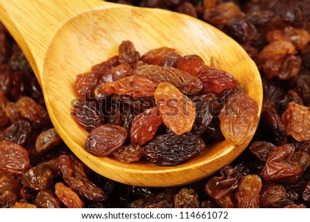raisins and  wooden  spoon close- up food background - stock photo