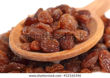 Raisins on wooden spoon. Isolated on white background. Macro. - stock photo