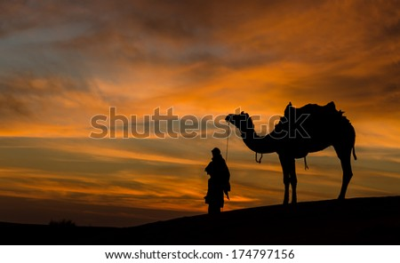 Rajasthan desert with dramatic sky with camel and man  - stock photo