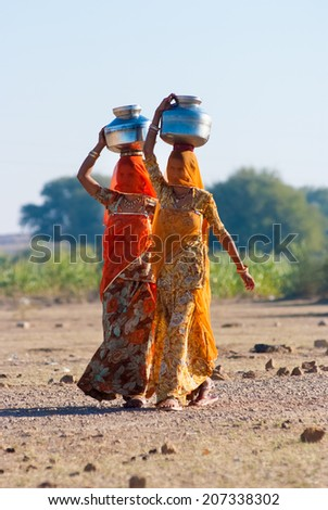 RAJASTHAN, INDIA-FEB 27: women lugging a water pot on their head on February 27, 2013 in Rajasthan, India. Due to the lack of piped water, poor tribals have to fetch water from its natural sources. - stock photo