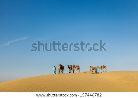 Rajasthan travel background - Three cameleers (camel drivers) with camels in dunes of Thar desert. Jaisalmer, Rajasthan, India - stock photo