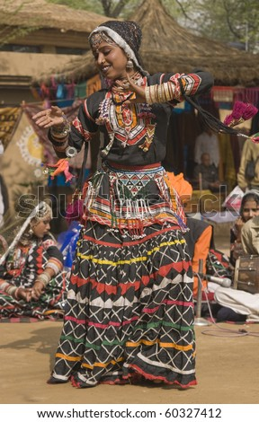 Rajasthani dancer in ornate black costume trimmed with beads and sequins performing at the Sarujkund Fair near Delhi in India.