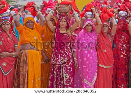 RAJSAMAND, INDIA - MARCH 7, 2015: Women gathered at the start of a procession during the Hindu festival of Gangaur which lasts for 16 days and is marked throughout Rajasthan to celebrate marriage - stock photo