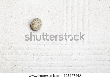 Raked sand garden with pebble - zen or meditation concept - stock photo