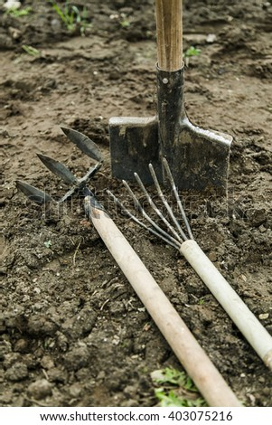 rakes, shovel and other items for the garden lying on the ground - stock photo
