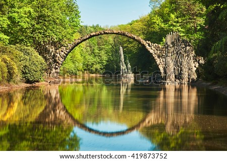 Rakotzbrucke also known as Devilâ??s Bridge in Kromlau in Germany. Reflection of the bridge in the water create a full circle. - stock photo