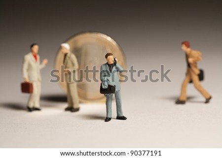 Rallying Around The Euro, miniature model businessmen standing around an upright euro coin in consultation and discussion. - stock photo
