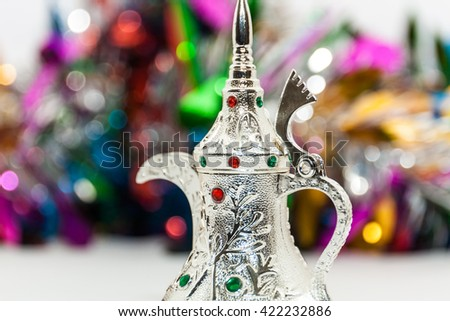 Ramadan, Eid concept - Silver arabic coffee pot in colorful out of focus background - stock photo