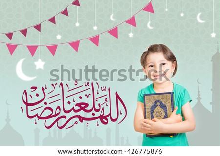 Ramadan Greeting Card -  Translation : May Allah make us reach Ramadan Muslim - Happy young Muslim girl holding Quraan (Holy book) - Ready for Ramadan - stock photo
