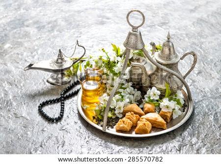 Ramadan kareem. Eid mubarak. Islamic holidays decoration. Oriental hospitality concept. Tea glasses and pot, traditional delight baklava - stock photo