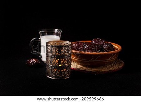 Ramadan lamp and dates with cup of milk and rosary, still life on black background  - stock photo