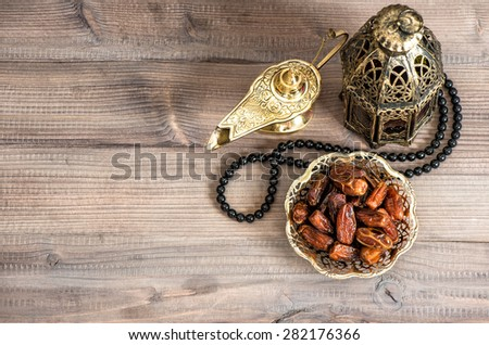 Ramadan lamp, rosary and dates on wooden background. Festive still life with oriental lantern - stock photo