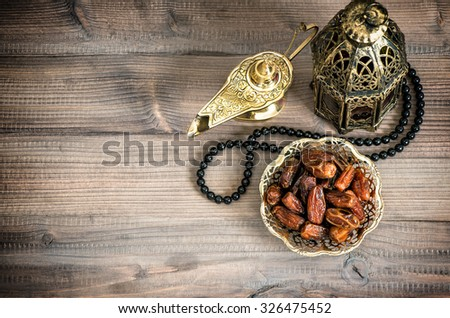 Ramadan lamp, rosary and dates on wooden background. Festive still life with oriental lantern. Vintage style toned picture with vignette - stock photo